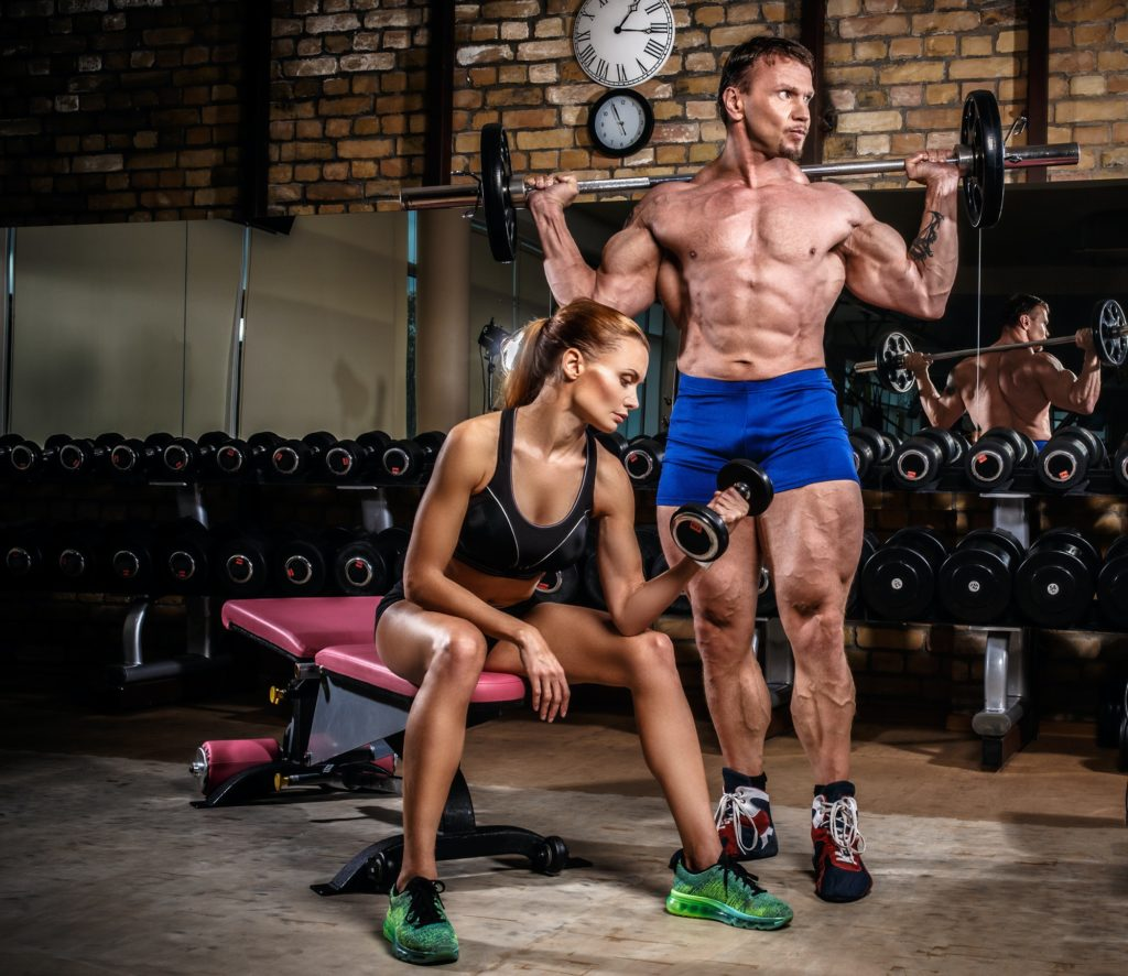Sports couple is working out at gym.