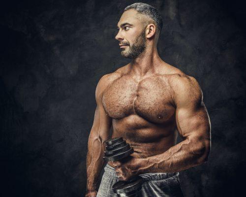 Adult caucasian muscular bodybuilder in a studio