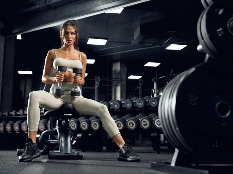 Female bodybuilder training with dumbbells